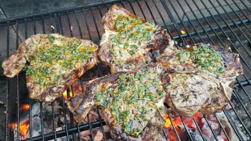Veal T-Bone Steaks with herby garlic grilling oil cook on the barbecue